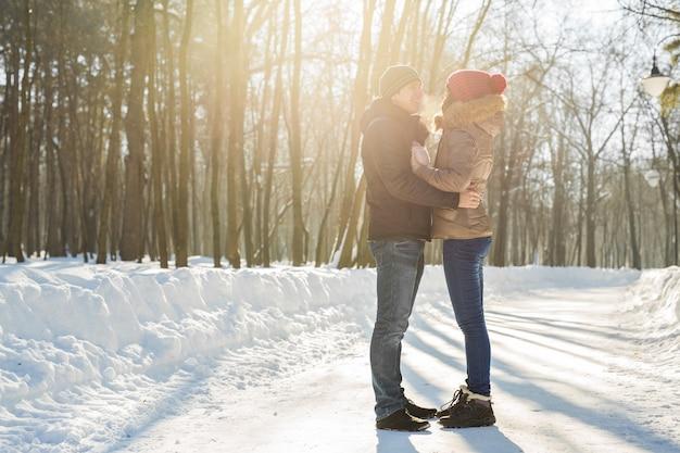 Jovem casal se abraçando e beijando no parque no inverno.