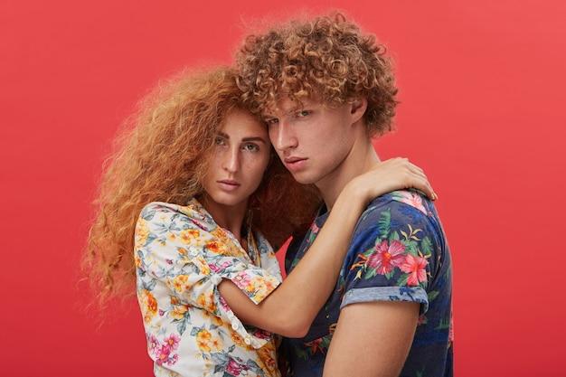 Jovem casal se abraçando e posando isolado no vermelho