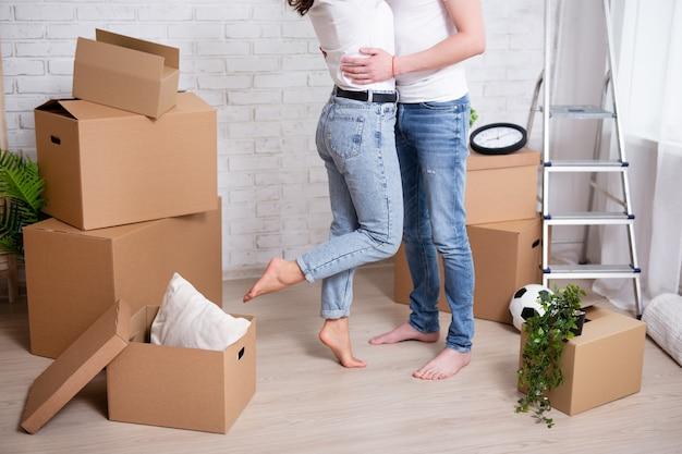 Jovem casal se abraçando em sua nova casa ou apartamento