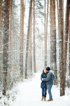Jovem casal se abraçando na floresta de inverno. férias de inverno. viagem de fim de semana. espaço para texto. cores naturais, foco seletivo.