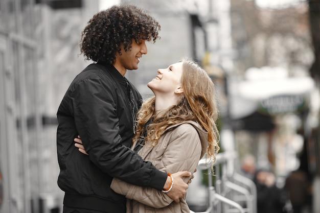 Jovem casal se abraçando na rua usando casacos.