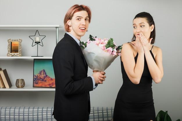 Jovem casal se abraçou no dia da mulher feliz com sussurros de uma mulher de buquê em pé na sala de estar
