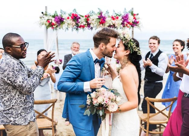 Jovem casal se beijando na recepção do casamento