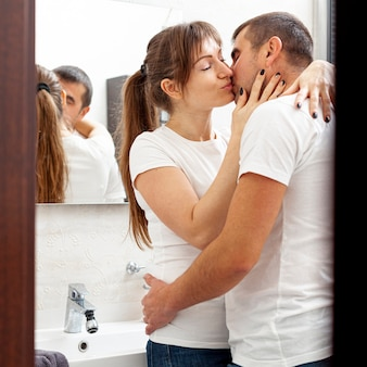 Jovem casal se beijando no banheiro