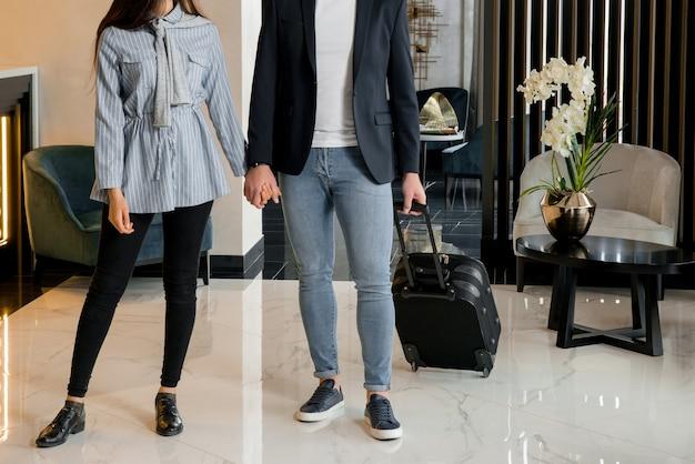 Jovem casal se despedindo em pé no saguão do hotel antes de o homem sair