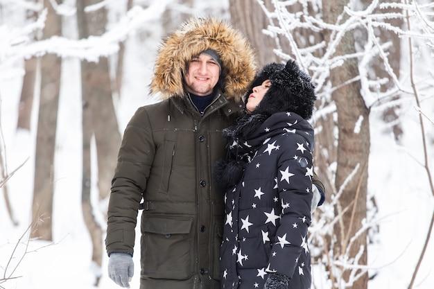 Jovem casal se diverte em um parque nevado, temporada de inverno