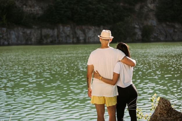 Jovem casal se divertindo à beira do rio em um dia ensolarado