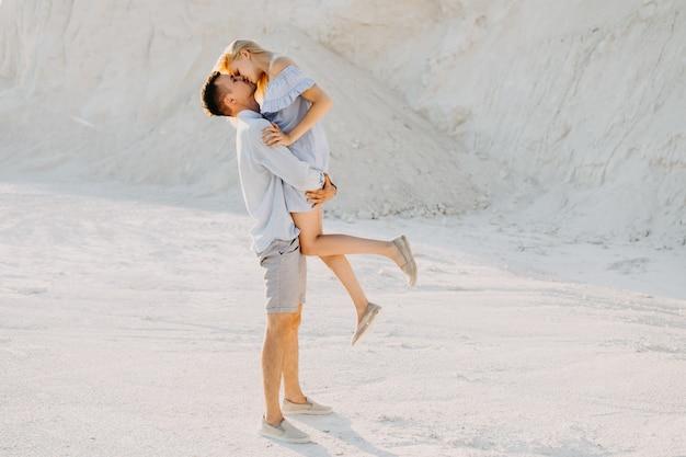 Jovem casal se divertindo, ao ar livre. homem segurando mulher nos braços, beijando.