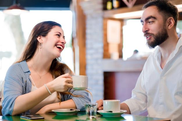 Jovem casal se divertindo enquanto bebe uma xícara de café juntos em uma cafeteria.
