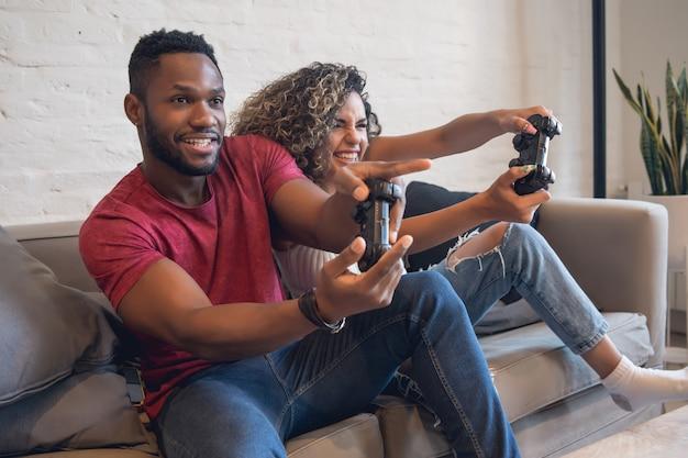 Jovem casal se divertindo enquanto jogava videogame juntos em casa.