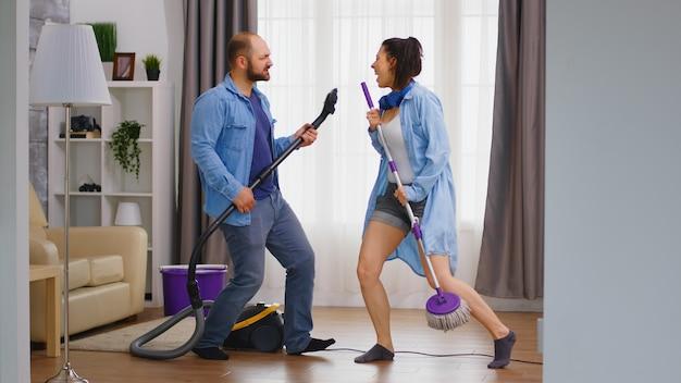 Jovem casal se divertindo fazendo tarefas domésticas usando aspirador de pó e esfregão como instrumentos musicais.