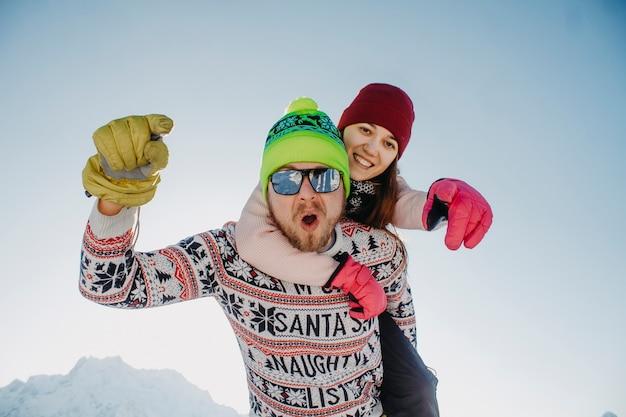 Jovem casal se divertindo nas montanhas nas férias de inverno.