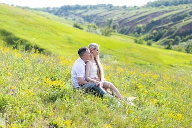 Jovem casal se divertir e brincar na grama. mulher com as mãos abertas deitada sobre o amante, sorrindo