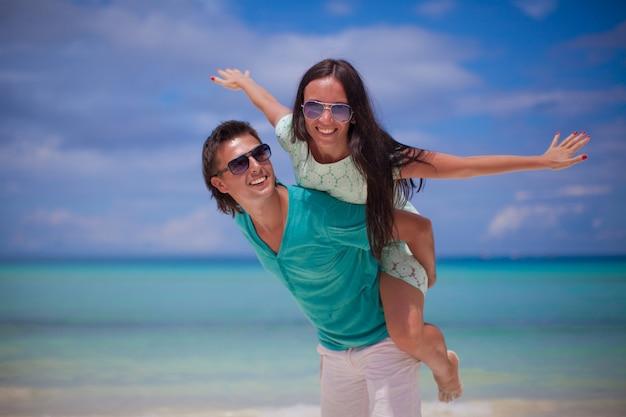 Jovem casal se divertir na praia de areia branca