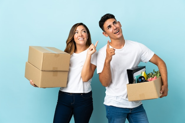 Jovem casal se mudando para a nova casa entre as caixas em azul apontando com o dedo indicador uma ótima ideia