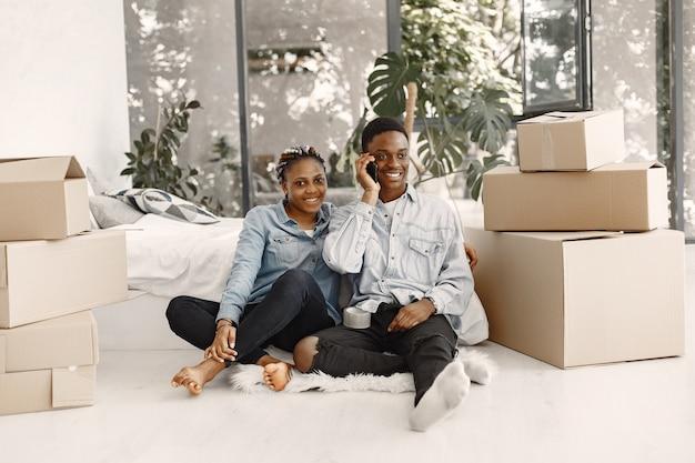 Jovem casal se mudando para a nova casa juntos. casal afro-americano com caixas de papelão.