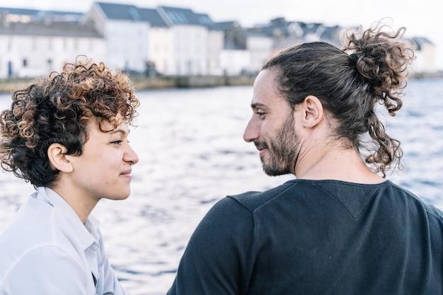 Jovem casal se olhando com o mar fora de foco
