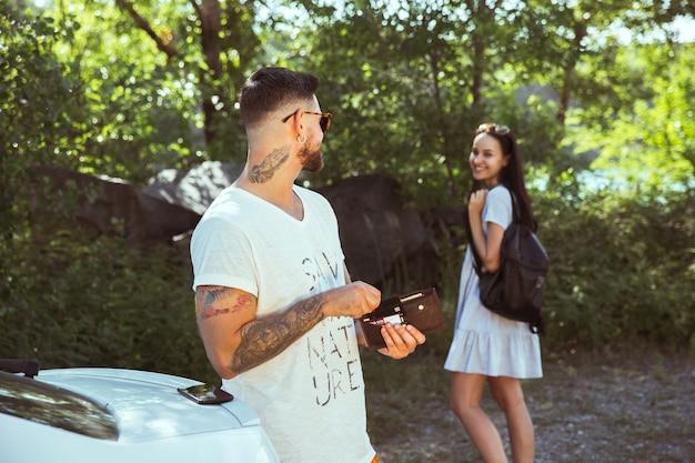 Jovem casal se preparando para as férias em um dia ensolarado de verão. mulher e homem sorrindo e passando algum tempo juntos na floresta. conceito de relacionamento, férias, verão, feriado, fim de semana, lua de mel.