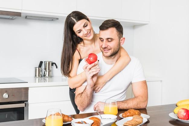 Jovem casal segurando a maçã na mão enquanto tomando café da manhã