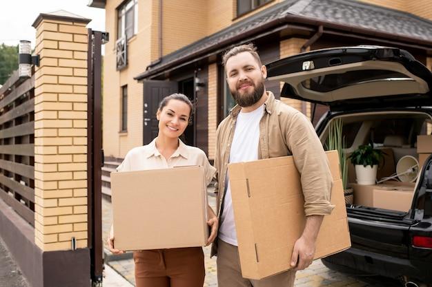 Jovem casal segurando caixas de mudança