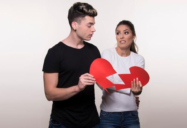 Jovem casal segurando metade do coração isolado no fundo branco