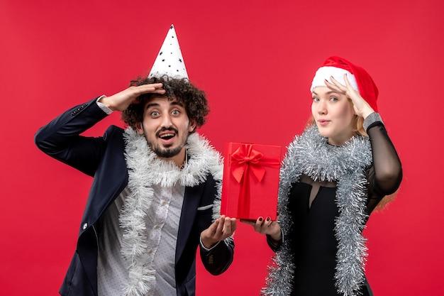 Jovem casal segurando o presente de ano novo na parede vermelha com as emoções do natal