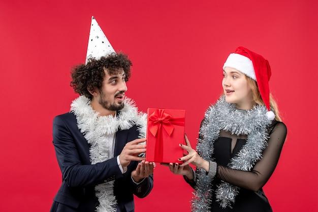 Jovem casal segurando o presente de ano novo na parede vermelha.