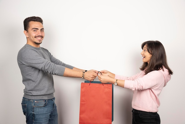 Jovem casal segurando sacolas de compras juntos.