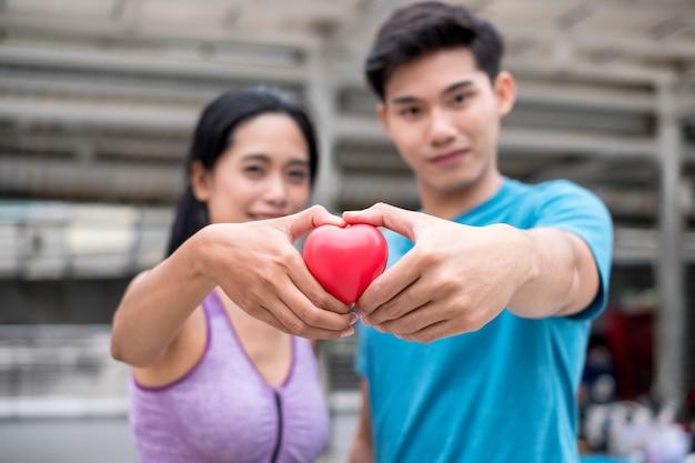 Jovem casal segurando um coração vermelho de articulação