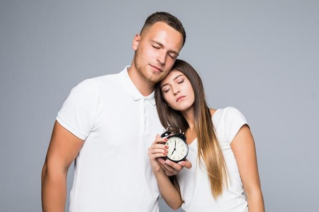 Jovem casal segurando um despertador vestido com camiseta branca e cansado.