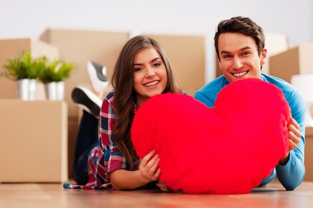 Jovem casal segurando um formato de coração em seu novo apartamento