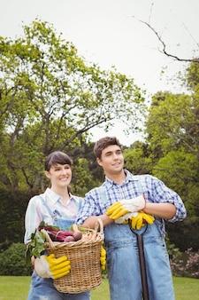 Jovem casal segurando uma cesta de legumes recém colhidos no jardim