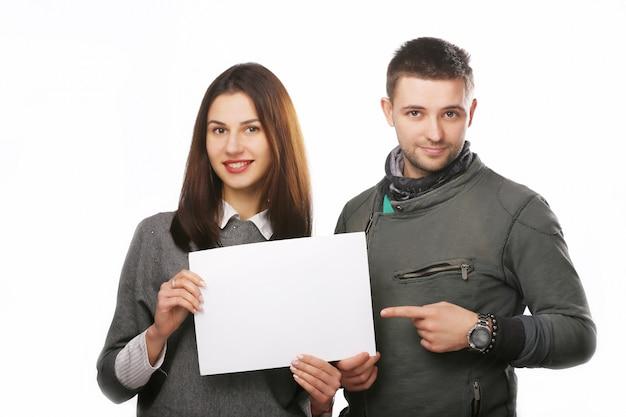 Jovem casal segurando uma folha de papel em branco.