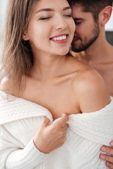 Jovem casal sensual apaixonado se abraçando e sorrindo em casa