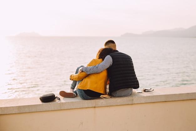 Jovem casal senta-se um ao lado do outro e olha para o mar.