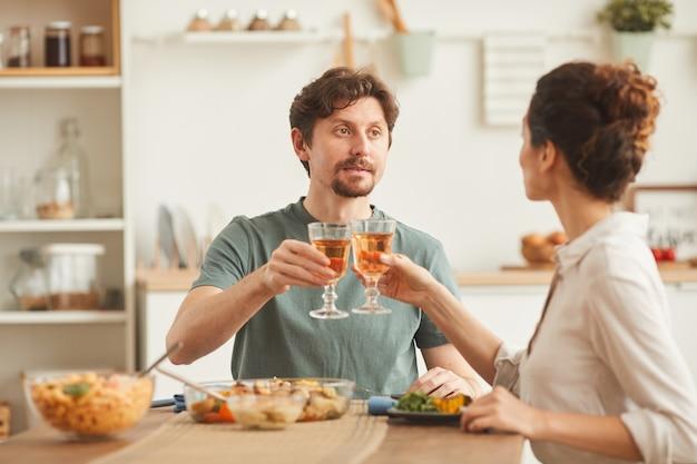 Jovem casal sentado à mesa bebendo vinho e jantando na cozinha doméstica
