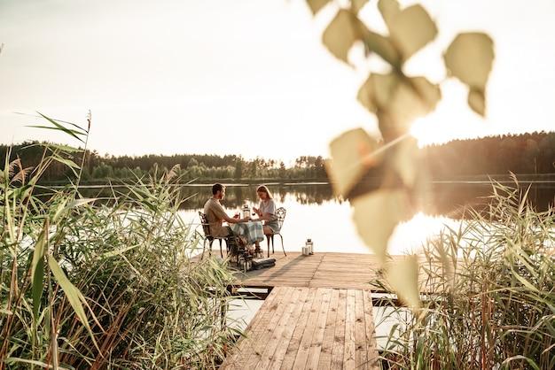 Jovem casal sentado à mesa, bebendo vinho juntos no cais de madeira no lago da floresta, comemorando o aniversário, de mãos dadas. o amor está no ar, o conceito de história de amor. jantar romântico com velas.