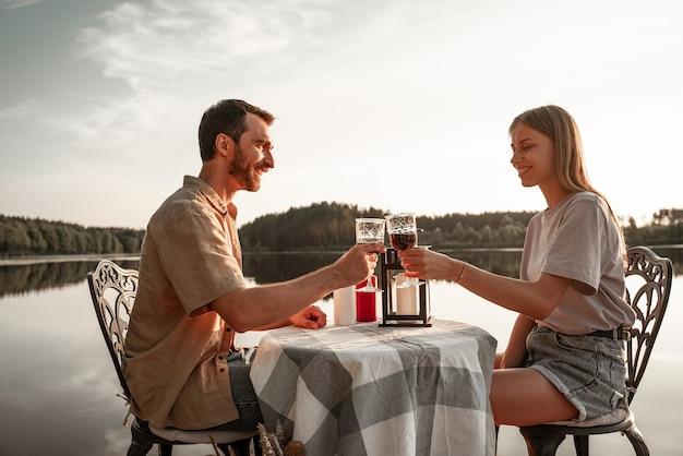 Jovem casal sentado à mesa, bebendo vinho juntos no lago da floresta, comemorando o aniversário, de mãos dadas. o amor está no ar, o conceito de história de amor. encontro romântico com velas. jantar para dois fora