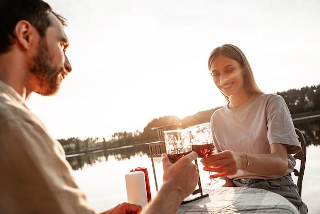 Jovem casal sentado à mesa, bebendo vinho juntos no lago da floresta, comemorando o aniversário. saúde. beber vinho com o namorado, jantar romântico juntos. conceito de história de amor. encontro com velas.
