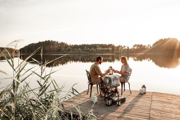 Jovem casal sentado à mesa passa algum tempo juntos no cais de madeira no lago da floresta, comemorando o aniversário, bebendo vinho. o amor está no ar, o conceito de história de amor. encontro romântico no lago com velas.