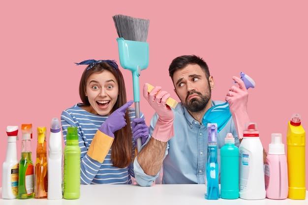 Jovem casal sentado ao lado de produtos de limpeza