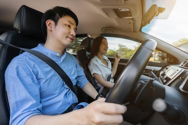Jovem casal sentado e dirigindo um carro