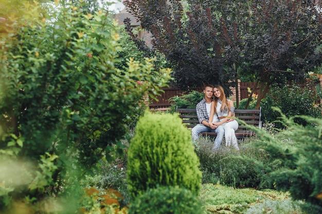 Jovem casal sentado em um banco no parque olhando para a frente
