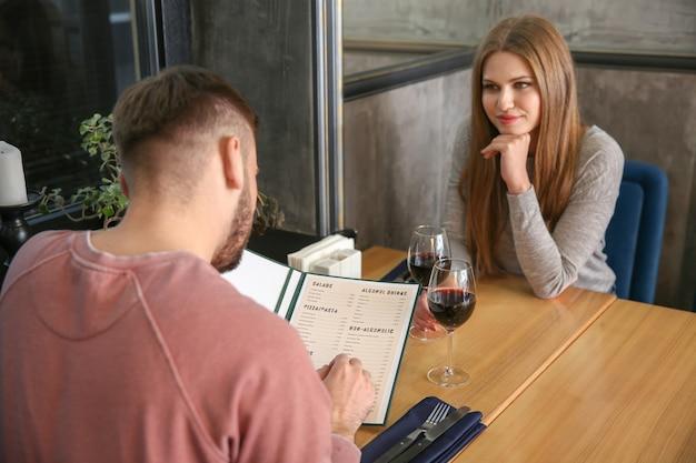 Jovem casal sentado em um restaurante com cardápio