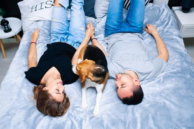 Jovem casal sentado em uma cama no quarto, abraçando. perto deles está o cachorro deles. animal doméstico beagle