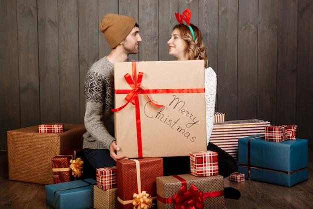 Jovem casal sentado entre caixas de presente de natal sobre parede de madeira