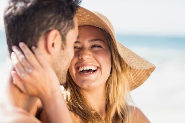Jovem casal sentado na areia