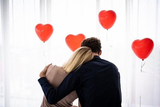 Jovem casal sentado na cama com balões em forma de coração vermelho