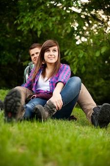 Jovem casal sentado na clareira