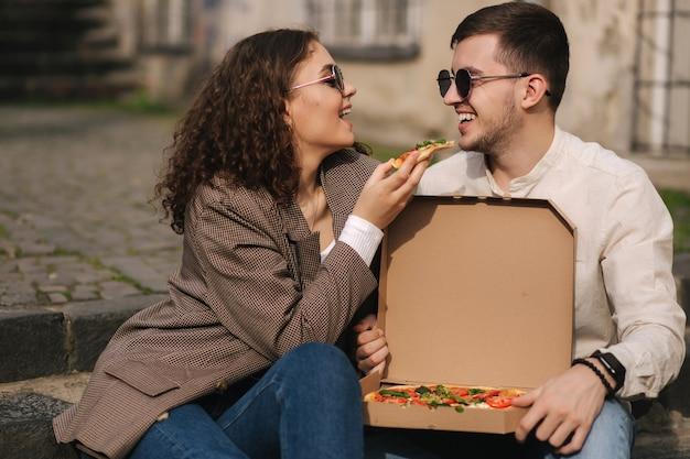 Jovem casal sentado na escada ao ar livre comendo pizza